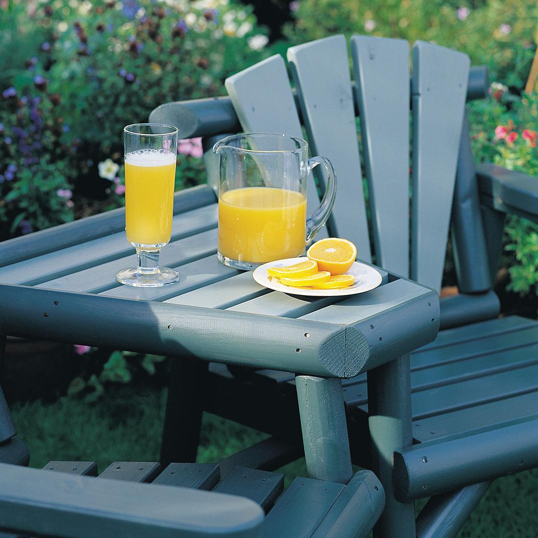 nærbilde av en blå sittegruppe i hagen med juice på bordet