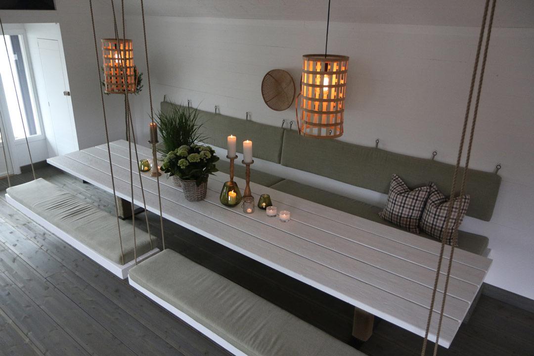 nymalt bord og benker hengende fra taket i hytte