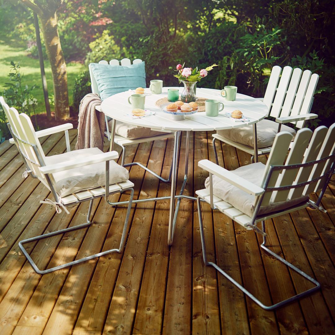 Luse utemøbler på en terrasse med frodig hage