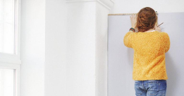 En dame med ryggen til som gjør forarbeid før maling