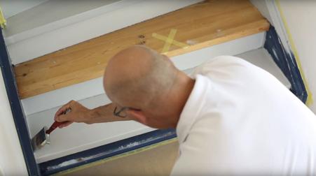 nærbilde av en mann som maler en trapp hvit