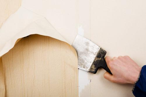 nærbilde av en hånd som fjerne gammel tapet fra veggen med en skrape