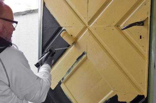 en mann maler en ytterdør gul